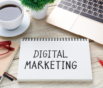 Digital marketing handwriting note with laptop pen and coffee cup on office desk